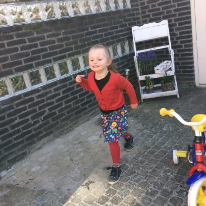 Isa speelt buiten in haar rimpelrok