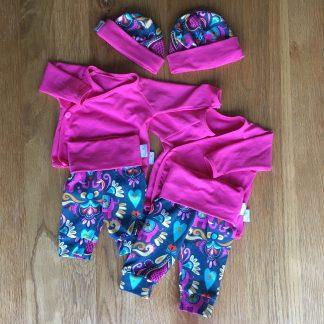 Twee setjes met kleding voor pasgeborenen. De truitjes zijn gemaakt van roze tricot en op de broekjes staat in Indiase print met olifanten in het donkergroen met andere felle kleuren