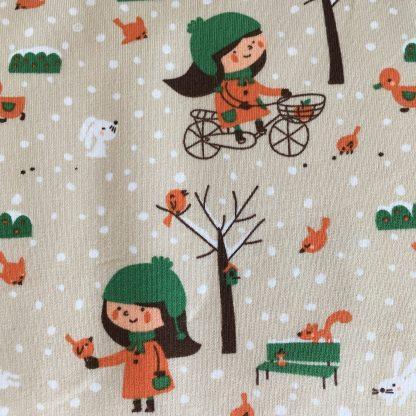 Een close up van de stof Wintergirl van Lillestof. Een crèmekleurige summersweat met een tekening van een winterse meisje op de fiets en met een volgetje in haar hand in oranje/groen tinten. Deze stof wordt gebruikt in de najaarscollectie 2018 van Kleine Benjamins.