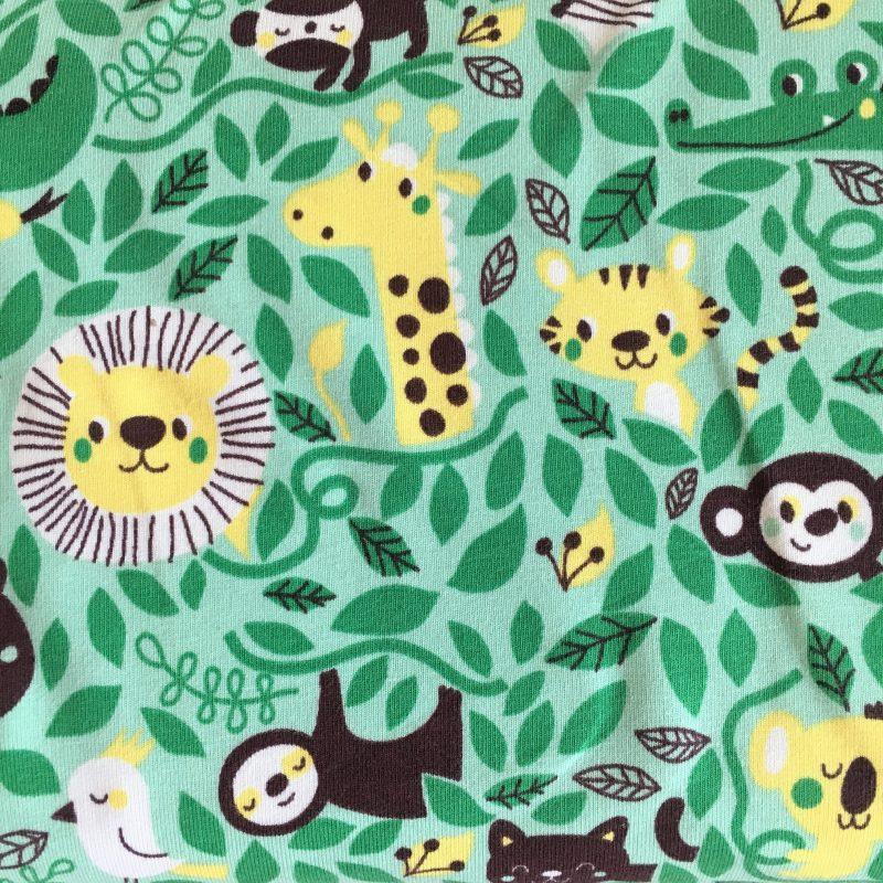 Een close up van de stof Rumble in the Jungle van Lillestof. Een lichtgroene summersweat met geel/bruine tekeningen van oerwoud dieren. Deze stof wordt gebruikt in de najaarscollectie 2018 van Kleine Benjamins.