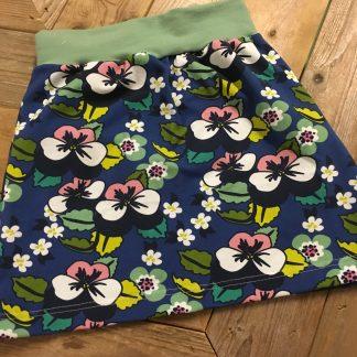 Een blauwe groene handgemaakte rok met viooltjes van biologisch tricot.