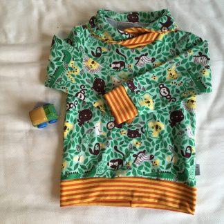 Een warme trui in de stof Rumble in the Jungle. Heeft een opdruk van jungledieren in bruin en geel tussen groene bladeren. Biologische summersweat van Lillestof, ontwerp van Sofilantjes.
