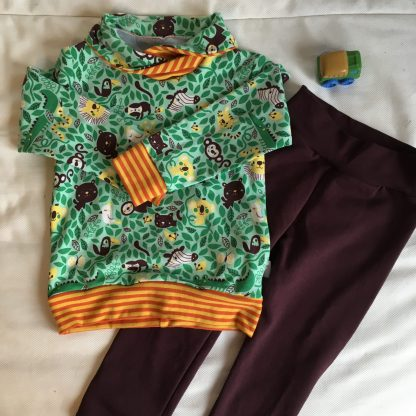 Een warme trui in de stof Rumble in the Jungle met een bijpassende espressobruine broek. Heeft een opdruk van jungledieren in bruin en geel tussen groene bladeren. Biologische summersweat van Lillestof, ontwerp van Sofilantjes.