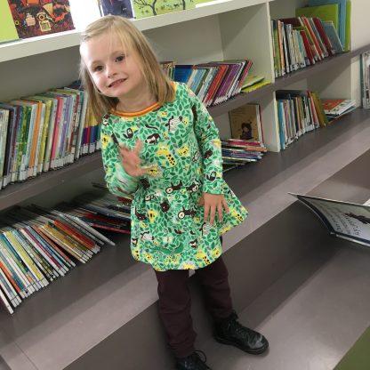 Een meisje van zes voor de boekenkast bij de bieb. Zij draagt een tuniek met jungledieren in combinatie met een espressobruine broek.