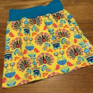Op deze handgemaakte rok pauwen staat een drukke print, die zo uit India lijkt te komen. Gewaagd design, en erg kleurrijk op een knalgele basis.