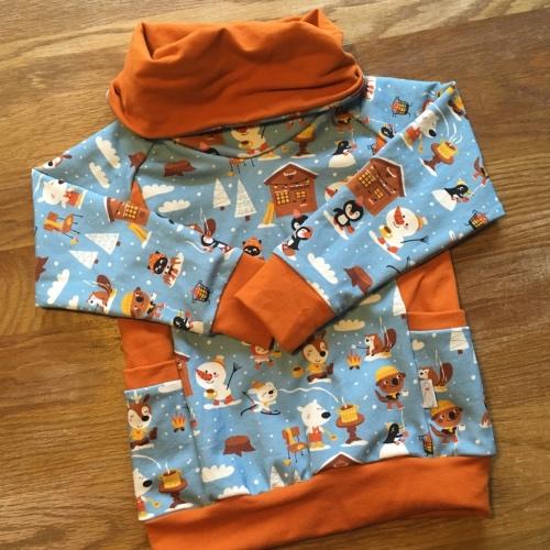 Een flatlat van een trui van biologische sweaterstof. Een blauwe trui met getekende afbeeldingen van dieren die warme chocomel drinken met kaneeloranje accenten