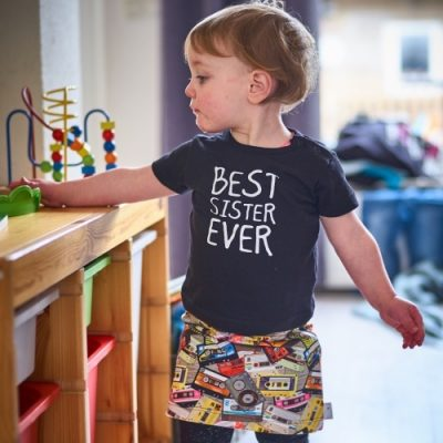 Meisje bij een kast met speelgoed. Zij draagt een zwart t-shirt en een handgemaakte rok met een print van retro cassettebandjes