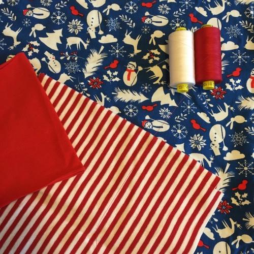 Kerststof blauw met witte kerst figuren en rode accenten. Goed te combineren met effen rood of rood witte strepen