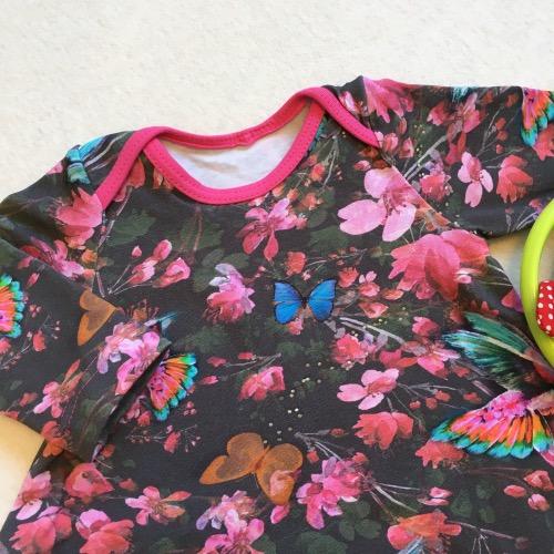 T-shirtjurk met kleurige roze bloemen en vogels op een donker achtergrond