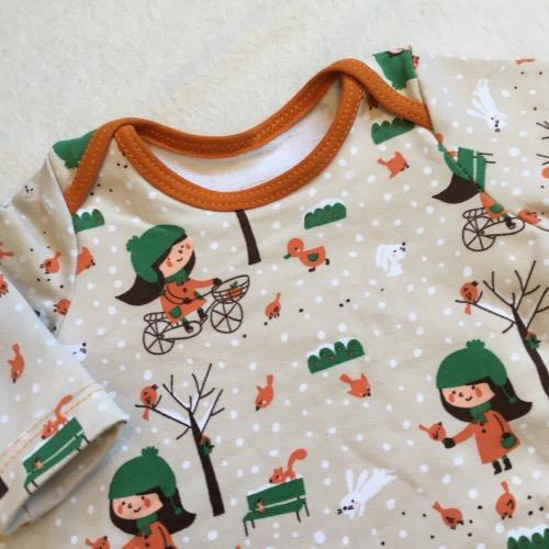 Wijdvallende jurk met oranjetinten en afbeeldingen van een meisje in de winter
